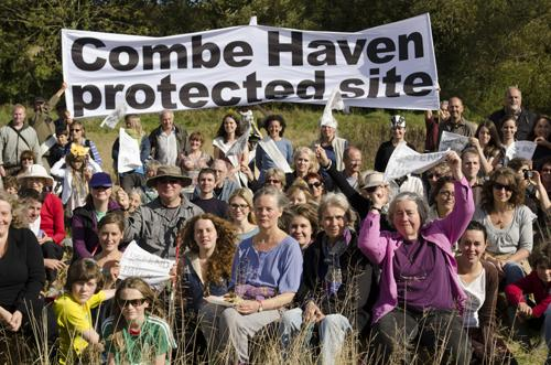 Campers at Combe Haven Defenders hold up a banner.
