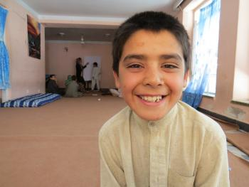 10-year-old Afghan Street Kid Mubasir smiles despite his difficulties.