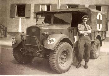 Frank J. Stevens, a Friends Ambulance Unit ambulance driver, with his vehicle in Wolfsburg, Germany, ?1945